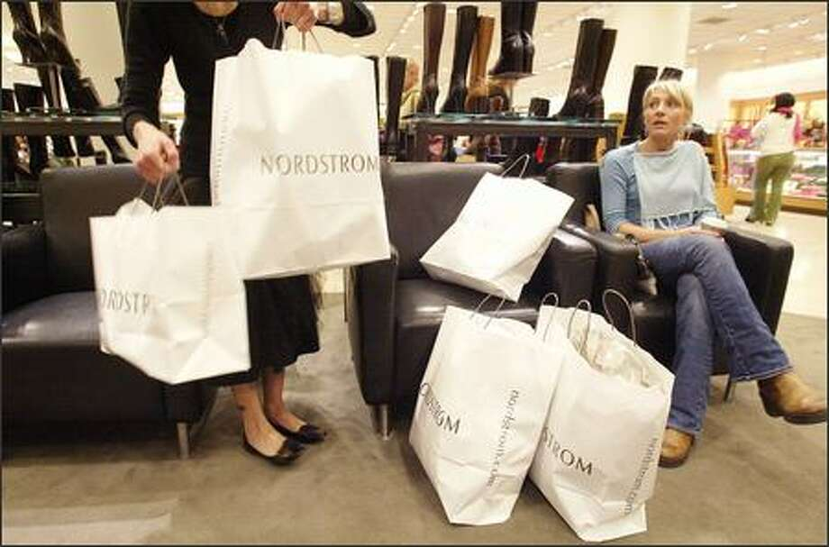 Nordstrom saleswoman Sara Jane Pignolet, left, helps shopper Ashley Hankins, right, gather her bags at the downtown Nordstrom store yesterday. Photo: Mike Urban, Seattle Post-Intelligencer / Seattle Post-Intelligencer