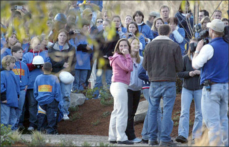Crowds gather to watch Roseanne Dore, center, and her daughters' reaction to their new home in Kingston yesterday. The house was built in five days. (Carolyn J. Yaschur / The Sun) Photo: Associated Press / THE SUN