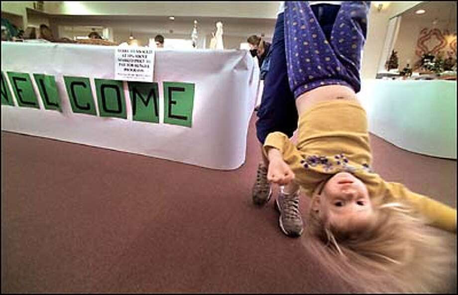 Two-year-old Rachel Larsen enjoys a different perspective on things at the hands of her sister, Jennifer, 12. The two girls were attending the 22nd annual Festival of Hope yesterday in Wallingford. The festival raises money for hunger relief and other causes. Photo: Melina Mara, Seattle Post-Intelligencer / Seattle Post-Intelligencer