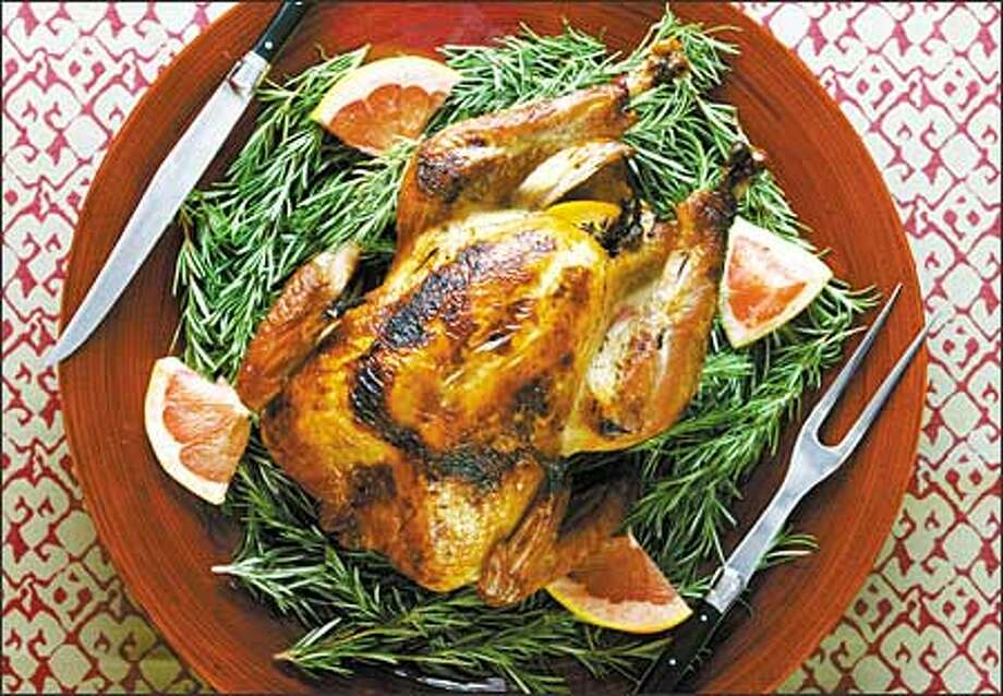 A roasted turkey nestles invitingly in a bed of rosemary and grapefruit wedges. When planning your dinner, allow 1 pound of turkey per person -- enough for seconds and leftovers. Photo: Paul Joseph Brown, Seattle Post-Intelligencer / Seattle Post-Intelligencer