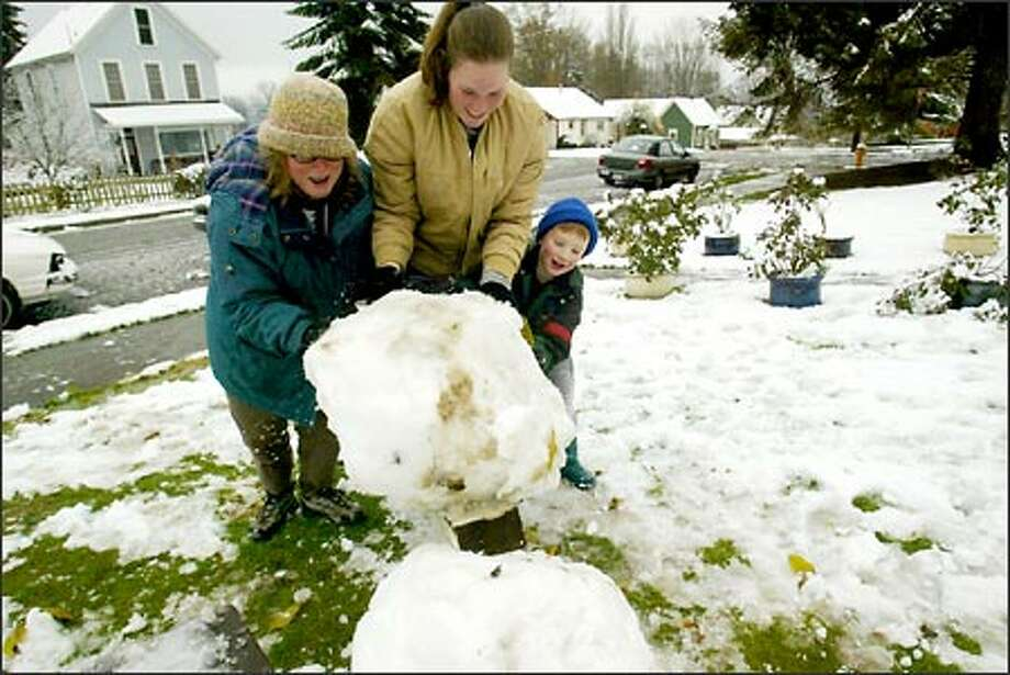 Nancy Chadwick, left, and her children Kristin, 21, and Dickey, 5, build a snowman yesterday. Photo: Grant M. Haller, Seattle Post-Intelligencer / Seattle Post-Intelligencer