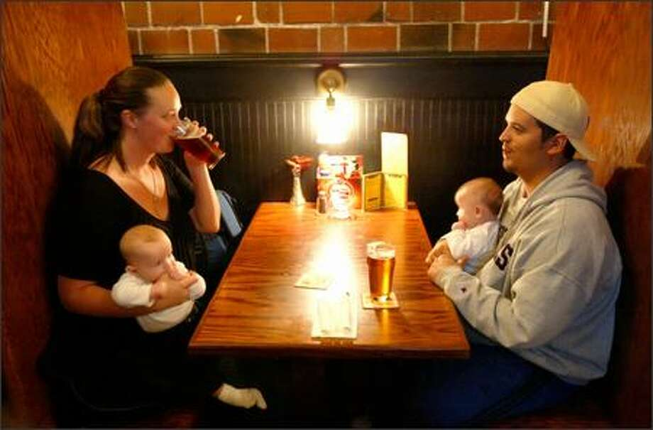 Oceania and Chaz Welsh enjoy a pair of pints and quality time with their twins, 4-month-old Nicolai, left, and Carlo, at the Elliott Bay Brewery Pub in West Seattle. Photo: Joshua Trujillo, Seattlepi.com / seattlepi.com