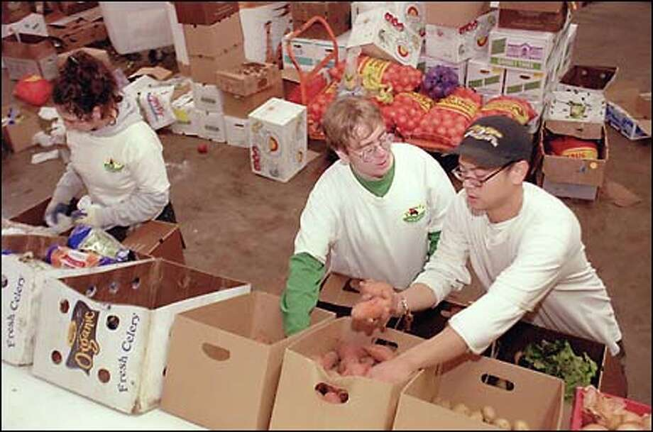 Chayla Thornton, Mathew Payne and B.J. Tiglao load boxes of fruit and vegetables at Pioneer Organics for home delivery. Pioneer Organics, which has expanded from 800 customers to about 1,400 in the past six months, outgrew its Fremont location and moved to a bigger warehouse in Ballard this week. The new warehouse, at 901 N.W. 49th St., has 5,500 square feet, more than twice the size of the company's old space. Pioneer has 14 employees and runs five trucks, including one fueled on natural gas. Boxes of organic produce, much of it generated by local farms, can be delivered weekly or every other week to area homes. Deliveries this week included carrots, celery, sage, thyme, kale, onions, parsley, apples, cranberries, oranges, pears, broccoli, yellow potatoes and yams, owner Ronny Bell said. Boxes range in price from about $25 to $50, depending on the size. Photo: Phil H. Webber, Seattle Post-Intelligencer / Seattle Post-Intelligencer