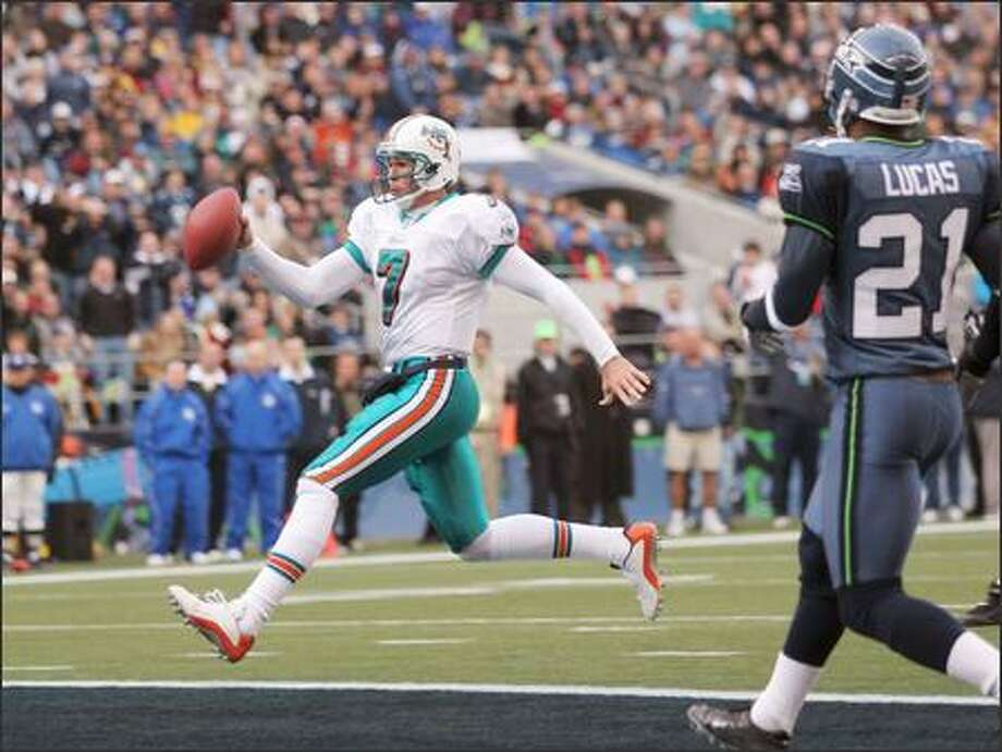 Miami Dolphins quarterback A.J. Feeley runs in for a touchdown with Seattle Seahawks' Ken Lucas watching from the side during the first quarter. (AP Photo/John Froschauer) Photo: Associated Press / Associated Press
