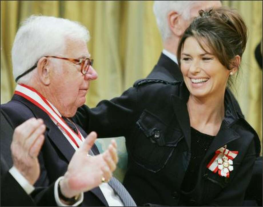 Country singer Shania Twain (here with neurosurgeon Ronald Tasker) was given her country's highest award on Friday, the Order of Canada, for her efforts to end child poverty. Too bad she left the country long ago, moving to Geneva with her husband and baby. Wait, didn't Celine Dion and Bryan Adams move to Europe, too? Photo: Associated Press / Associated Press