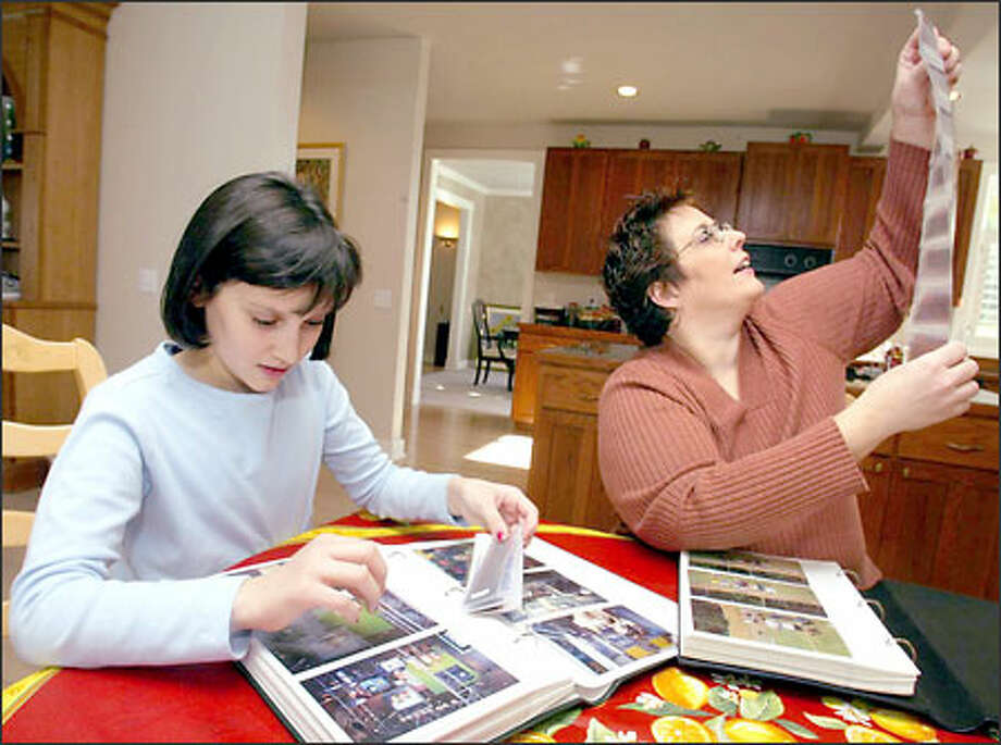 Samantha Graziadio and daughter Hannah, 11, organize family photos. Samantha won the Scott company's Chief Common Sense Officer contest. Photo: Grant M. Haller, Seattle Post-Intelligencer / Seattle Post-Intelligencer