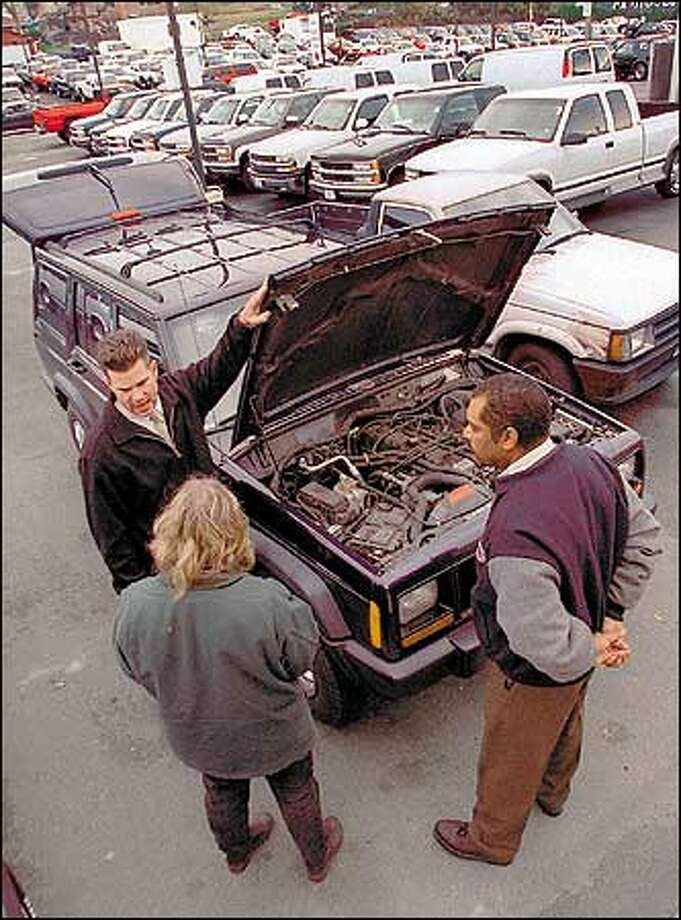 J.T. Curry, used-car sales manager, and sales representative Marvin Kasimat of Huling Bros in West Seattle show Susan James of Vashon a Jeep she is buying for use in her painting company. For her, excess inventory means a good deal. Photo: Phil H. Webber, Seattle Post-Intelligencer / Seattle Post-Intelligencer