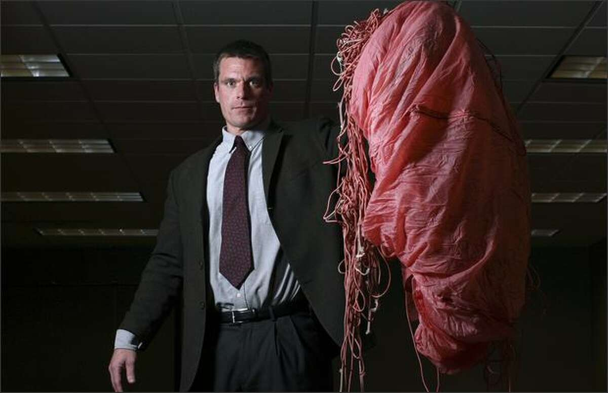FBI agent Larry Carr displays a parachute left behind by D.B. Cooper, part of the evidence in the 1971 hijacking case, at the FBI's Seattle office Wednesday. Cooper was given four chutes.