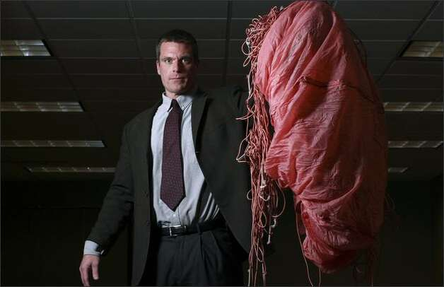 FBI agent Larry Carr displays a parachute left behind by D.B. Cooper, part of the evidence in the 1971 hijacking case, at the FBI's Seattle office Wednesday. Cooper was given four chutes. Photo: Andy Rogers, Seattle Post-Intelligencer / Seattle Post-Intelligencer