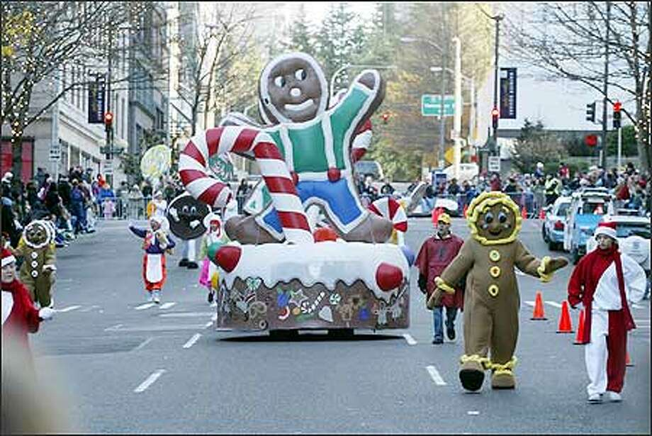 A gingerbread man and woman guide their float down University Street during last year's Thanksgiving Day parade. Photo: Phil H. Webber, Seattle Post-Intelligencer / Seattle Post-Intelligencer