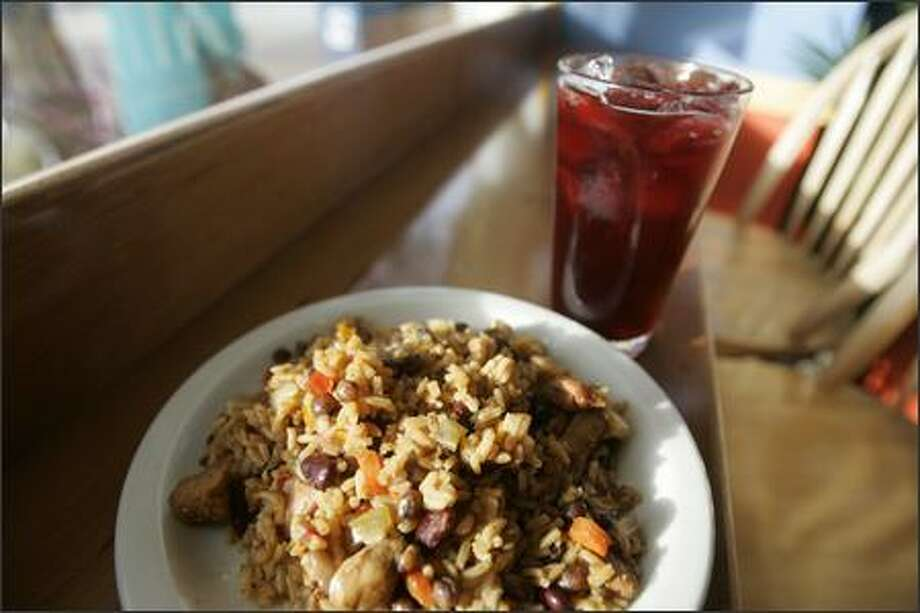 Pam's Kitchen serves up a plate of Chicken Pilau -- browned, seasoned chicken cooked in rice and pigeon peas -- and a glass of Sorrel, a juice made from dried hibiscus. Photo: Mike Kane, Seattle Post-Intelligencer / Seattle Post-Intelligencer