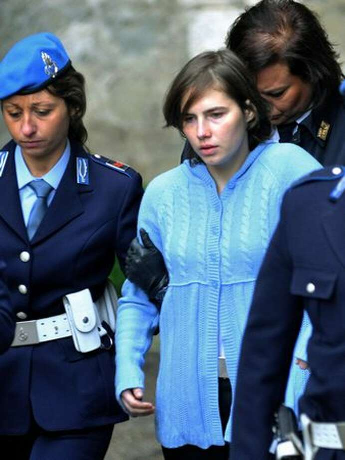 Amanda Knox, center, is escorted by penitentiary guards after a hearing for her appeals trial in Perugia, Italy. The former Seattle college student, 23, was convicted in December 2009 of killing her British roommate Meredith Kercher in a case that drew global attention. Knox was sentenced to 26 years in prison. (AP Photo/Stefano Medici) Photo: Associated Press / Associated Press