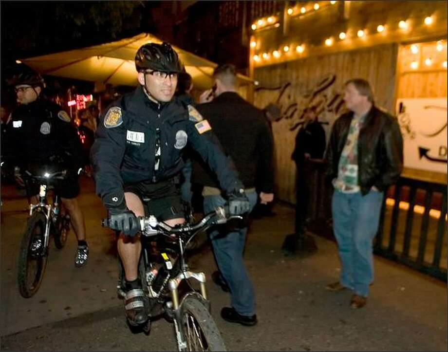 Seattle Police Officers Rob Cierley, left, and Raul Vaca cruise the Belltown bar scene. Other cities have modeled Seattle's program. Photo: Jim Bryant, Seattle Post-Intelligencer / Seattle Post-Intelligencer
