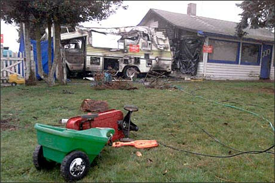A charred motor home in which two young brothers died serves as a backdrop for children's toys in the yard at the scene of the fire Sunday night in Sumner. Photo: Scott Eklund, Seattle Post-Intelligencer / Seattle Post-Intelligencer
