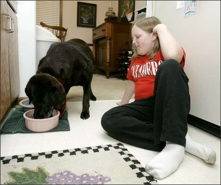 Ten-year-old Natalie Wickstrom feeds the family dog, Shasta, at home in Marietta, Ga. (AP Photo/Ric Feld) Photo: Associated Press / Associated Press