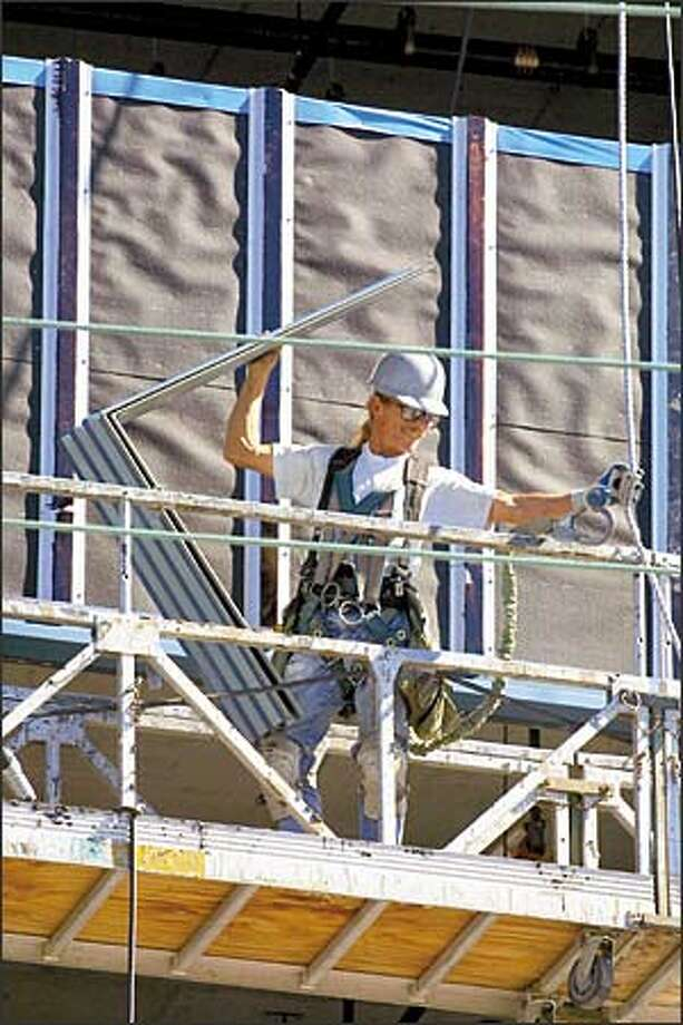 A worker prepares to place a corner of siding on the new 1616 Eastlake Building, which is in need of tenants. Photo: Phil H. Webber, Seattle Post-Intelligencer / Seattle Post-Intelligencer