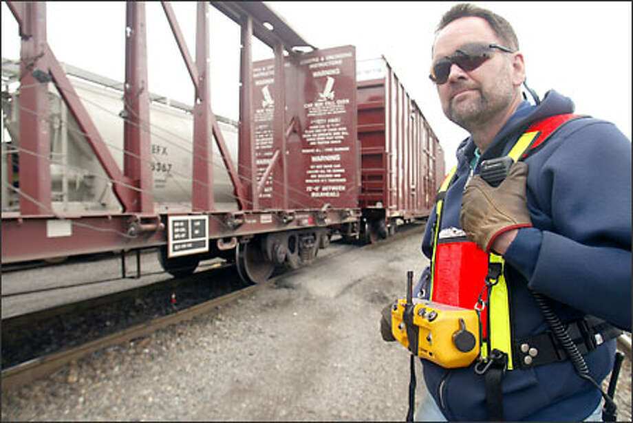 Switchman Wayne Reynolds moves trains from track to track at the Burlington Northern Santa Fe Stacy Street switching yard by remote control. Photo: Mike Urban, Seattle Post-Intelligencer / Seattle Post-Intelligencer