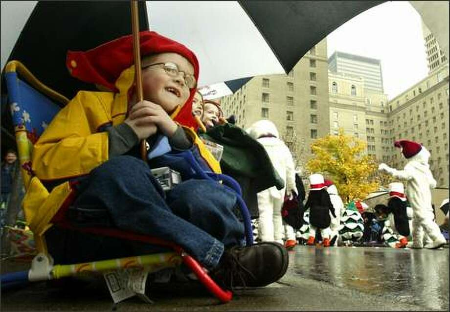 Tanner Mecham, 4, of Bellevue smiles as he catches a glimpse of Santa approaching on a float near the end of the Bon-Macy's Holiday Parade Friday, Nov. 28, 2003 in downtown Seattle. A steady rain didn't deter thousands of parade fans and holiday shoppers from heading downtown on the traditional first day of holiday shopping. (AP Photo/Ted S. Warren) Photo: Associated Press / Associated Press