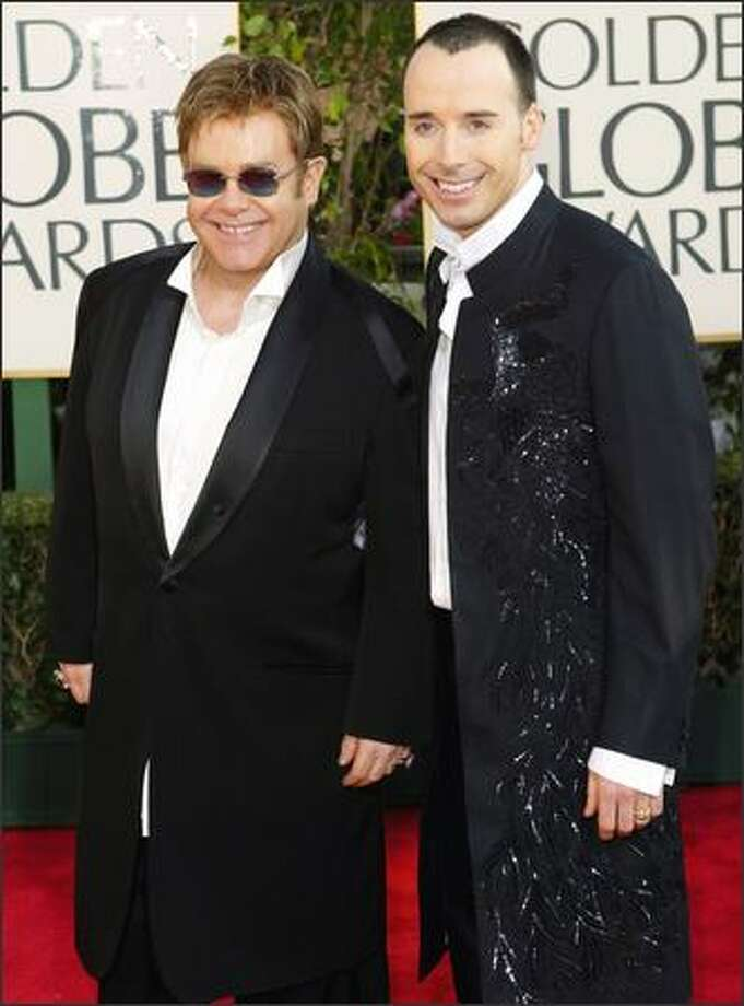 Elton John told Attitude magazine last week that he plans to unite in civil union with his longtime partner, Canadian filmmaker David Furnish (seen here with the singer last year at the Golden Globe Awards), in a small, private ceremony next month. Photo: Associated Press / Associated Press