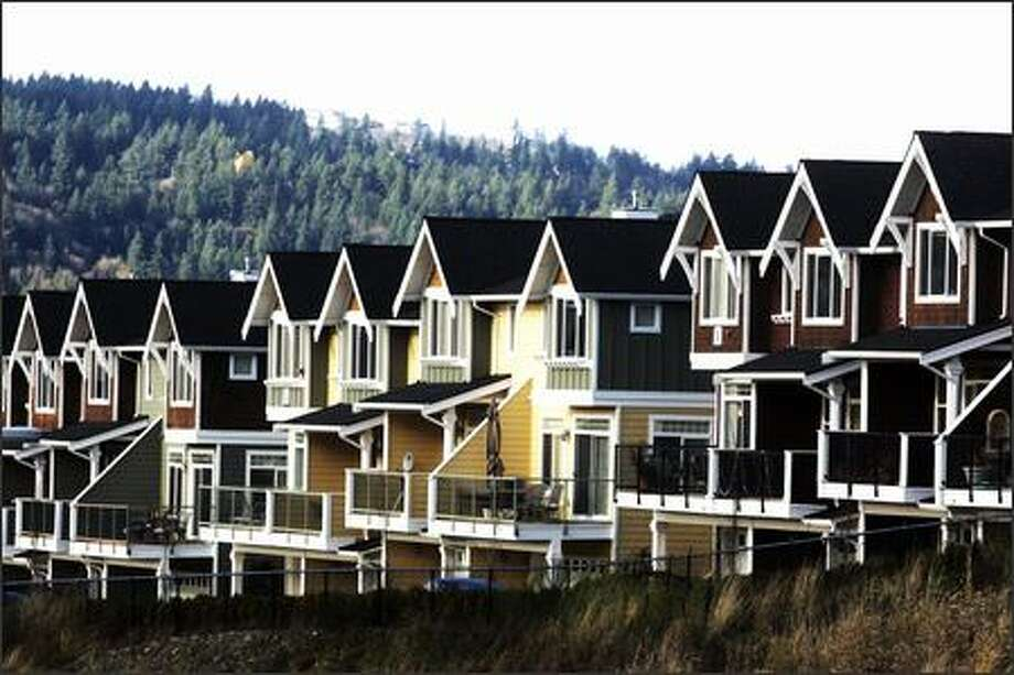 There's pleasure in architectural rhythm, but it morphs into deadly ennui when identical porches and window treatments and gables march on block after block, tier over tier ladled onto forested hillsides, such as with the Hamptons Pointe townhouses in Issaquah. Photo: Mike Kane, Seattle Post-Intelligencer / Seattle Post-Intelligencer