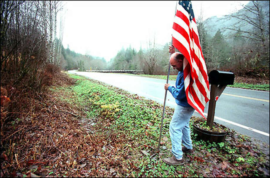 Gulf War veteran Jay Murray places a flag near the driveway to his family's home in Silverton. The town is scheduled to receive phone service next summer. Photo: Paul Joseph Brown, Seattle Post-Intelligencer / Seattle Post-Intelligencer