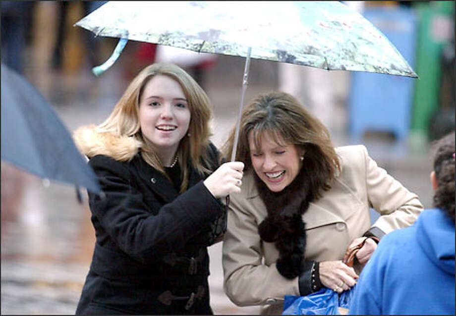 Melissa Sloan of Tacoma holds an umbrella for aunt Tammy Miell of Cle Elum as they dash across Fourth Avenue while joining throngs of shoppers in downtown Seattle. Photo: Gilbert W. Arias, Seattle Post-Intelligencer / Seattle Post-Intelligencer