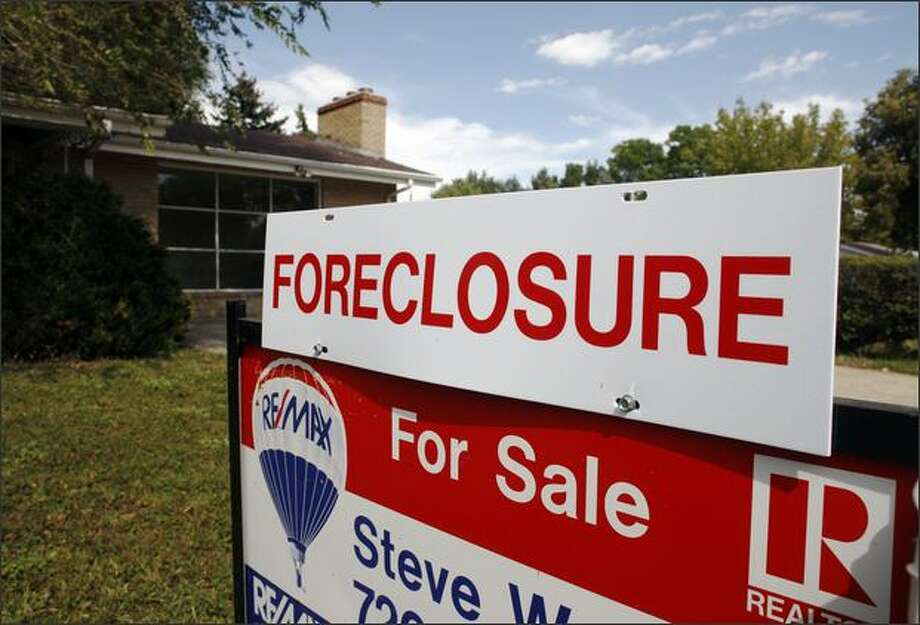 A foreclosure sign stands on top of a sale sign outside an existing home for sale in the west Denver suburb of Lakewood, Colo., on Sunday, Sept. 28, 2008. A widely watched index shows home prices dropping by the sharpest annual rate on record in the third quarter as foreclosures continued to flood the market and nervous homebuyers sat on the sidelines. Photo: Associated Press / Associated Press