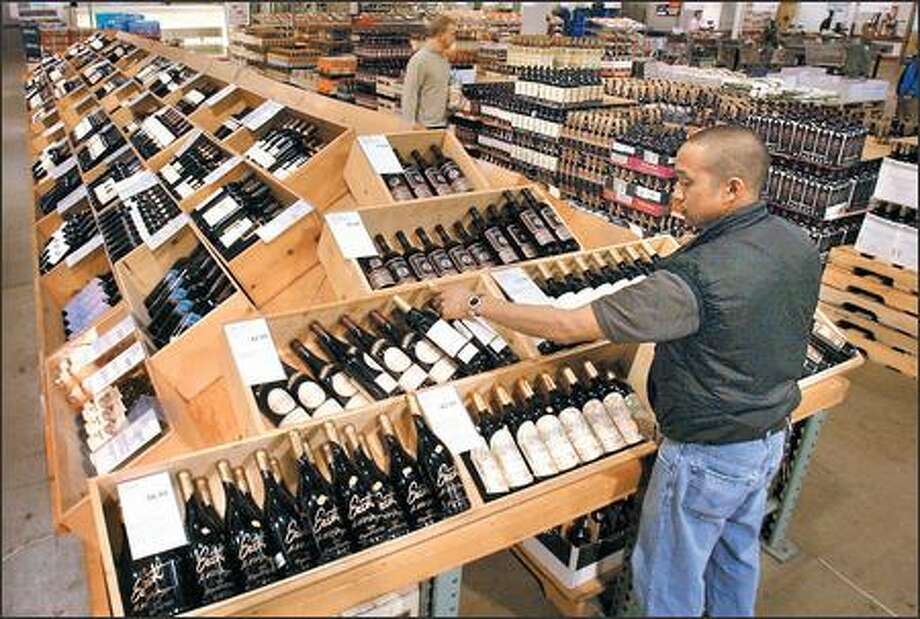 Fred Borja stocks wine at the Costco on Fourth Avenue South in Seattle. Costco is the country's largest wine seller. Photo: Grant M. Haller, Seattle Post-Intelligencer / Seattle Post-Intelligencer
