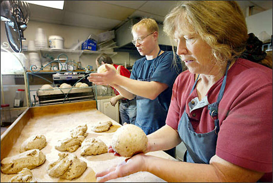 Peggy Boggs and her son, Ryan Ott, shape dough at Peggy's Bakery Organica in Sedro-Woolley. Purity and freshness of ingredients are their top priorities Photo: Dan DeLong, Seattle Post-Intelligencer / Seattle Post-Intelligencer