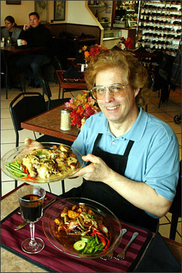 Don Wilson, owner of the Sterling Cafe, displays a couple of entrees: roasted chicken ($19.50) and, on the table, liver and onions ($17). A variety of organic wines is served in goblets. Photo: Phil H. Webber, Seattle Post-Intelligencer / Seattle Post-Intelligencer