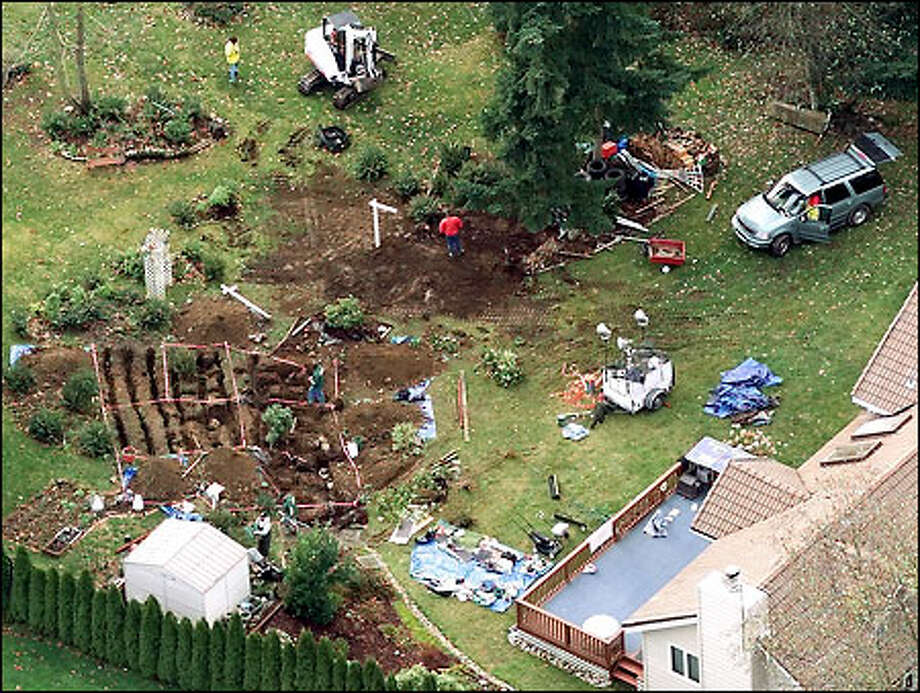 Police investigators excavate in the back yard of the Auburn home of Gary Ridgway looking for clues yesterday in the Green River killings. Photo: Mike Urban, Seattle Post-Intelligencer / Seattle Post-Intelligencer