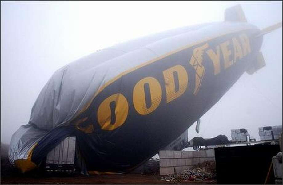 A Goodyear blimp lays at its crash site in Carson, Calif. Thursday, Dec. 4, 2003. The blimp came loose from its moorings, drifted into a parked truck and nose-dived into a fertilizer pile beside a plant nursery late Wednesday. A cameraman had a knee injury and was taken to a hospital, said Sgt. Paul Rice of the Los Angeles County Sheriff's Department. No one else aboard the 192-foot-long Spirit of America was injured. (AP Photo/John Hayes) Photo: Associated Press / Associated Press