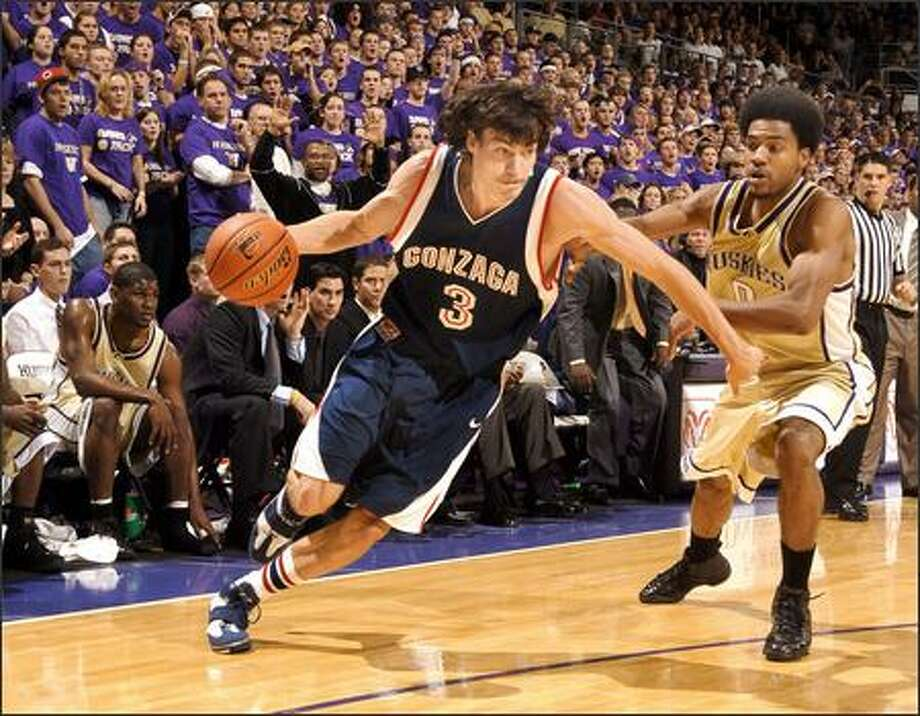 Gonzaga star Adam Morrison drives past the UW's Joel Smith during the first half at Edmundson Pavilion. It was Morrison's first loss to the UW. (Mark J. Rebilas, NewsCom)