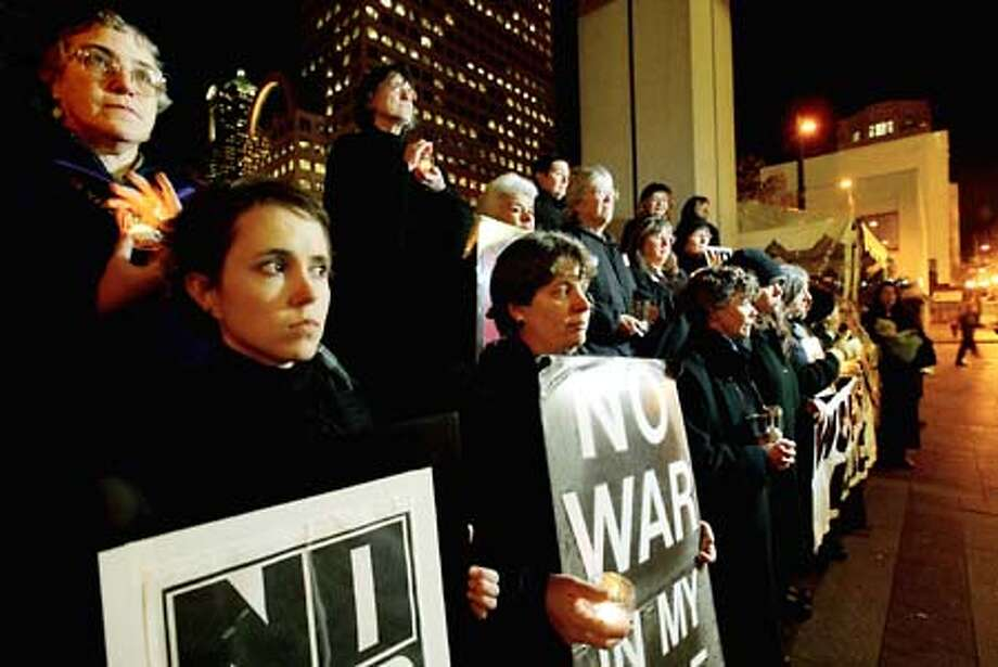 "Members of ""Women in Black"" hold their weekly silent vigil to protest the prospect of war in Iraq at Westlake Park in downtown Seattle. Photo: Dan DeLong, Seattle Post-Intelligencer / Seattle Post-Intelligencer"