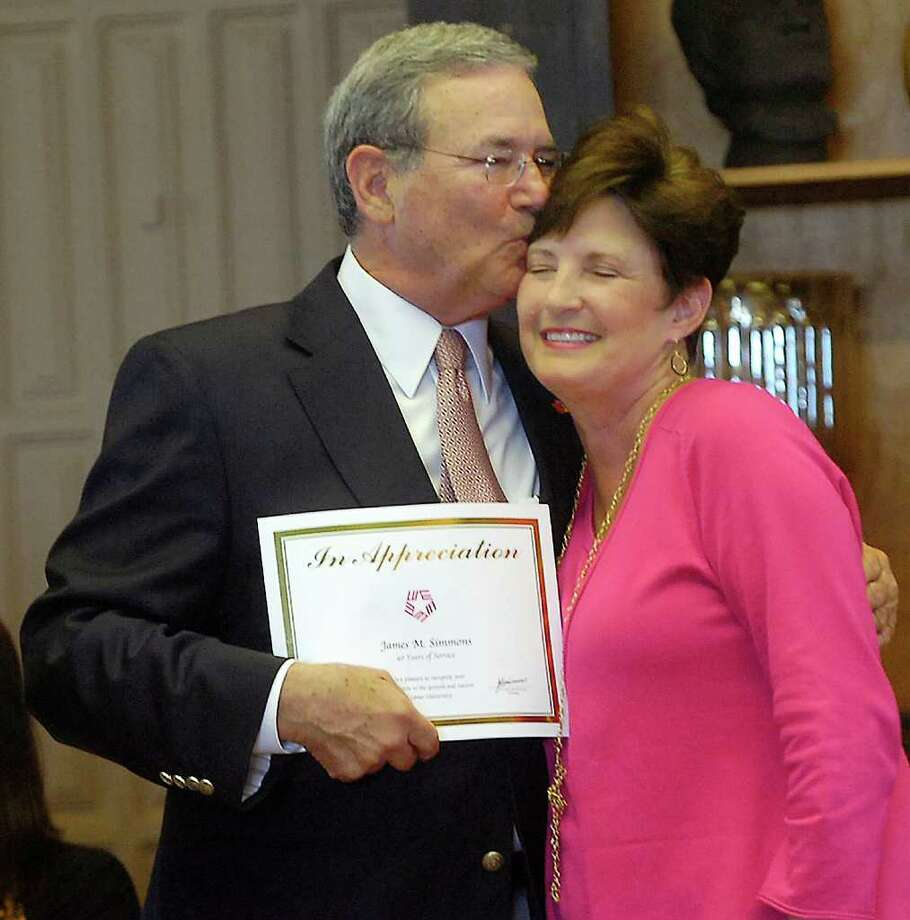 Forty Year Award recipient James M. Simmons, left, the President of Lamar University, gives  his wife Susan a kiss in front of the assembled crowd after she presented him with his award.  Lamar University honored 120 employees for their years of service to the university at a reception and program Tuesday morning, hosted by the Lamar University Staff Senate, in the University Reception Center on the eighth floor of the Mary and John Gray Library.    Dave Ryan/The Enterprise Photo: Dave Ryan / Beaumont