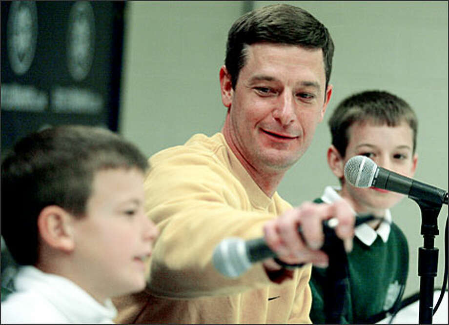 Mariners pitcher Jamie Moyer adjusts the microphone of his 9-year-old son Hutton during a news conference yesterday at Safeco Field, where Moyer discussed his three-year contract. Photo: Paul Joseph Brown, Seattle Post-Intelligencer / Seattle Post-Intelligencer