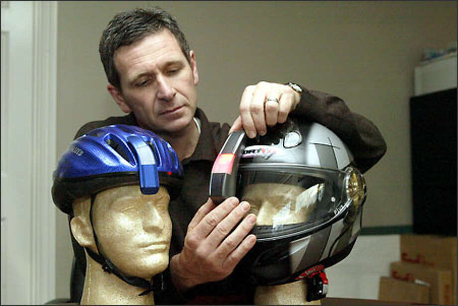 Dominic Dobson, president of Motion Research, shows how a heads-up display is mounted on a motorcycle helmet and, at left, a bicycle helmet. Photo: Phil H. Webber, Seattle Post-Intelligencer / Seattle Post-Intelligencer