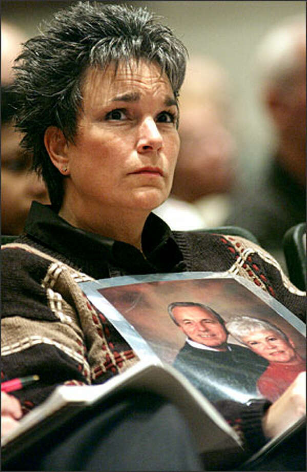 Julie Fisher of Eugene, Ore., holds a photo of her parents, Glenn and Barbara Haleberg, while attending yesterday's NTSB hearing disclosing results of the investigation into the crash that killed them and 86 others. Photo: Associated Press / Associated Press
