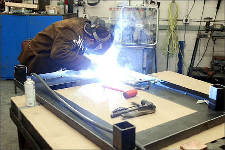 Chris McElroy welds a leg on a coffee table at Slliks Design in Auburn. This table will cost $1,200 at Slliks' new showroom in downtown Seattle. Photo: Phil H. Webber, Seattle Post-Intelligencer / Seattle Post-Intelligencer