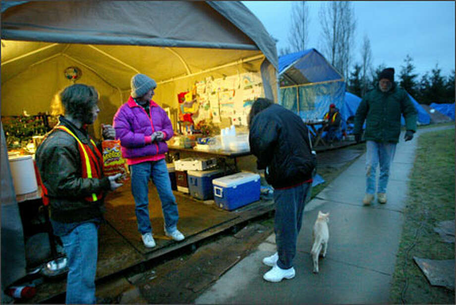 A few residents of Tent City 4 in Kirkland mill around the kitchen tent on a recent morning. Andy Broncato, left, serves as a security guard, a duty rotated among all residents. Photo: Karen Ducey, Seattle Post-Intelligencer / Seattle Post-Intelligencer