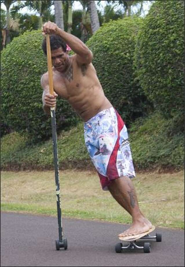 The Kahuna Big Stick Classic paddle pole is shown being used with a longboard. The stick paddle provides an upper-body workout.