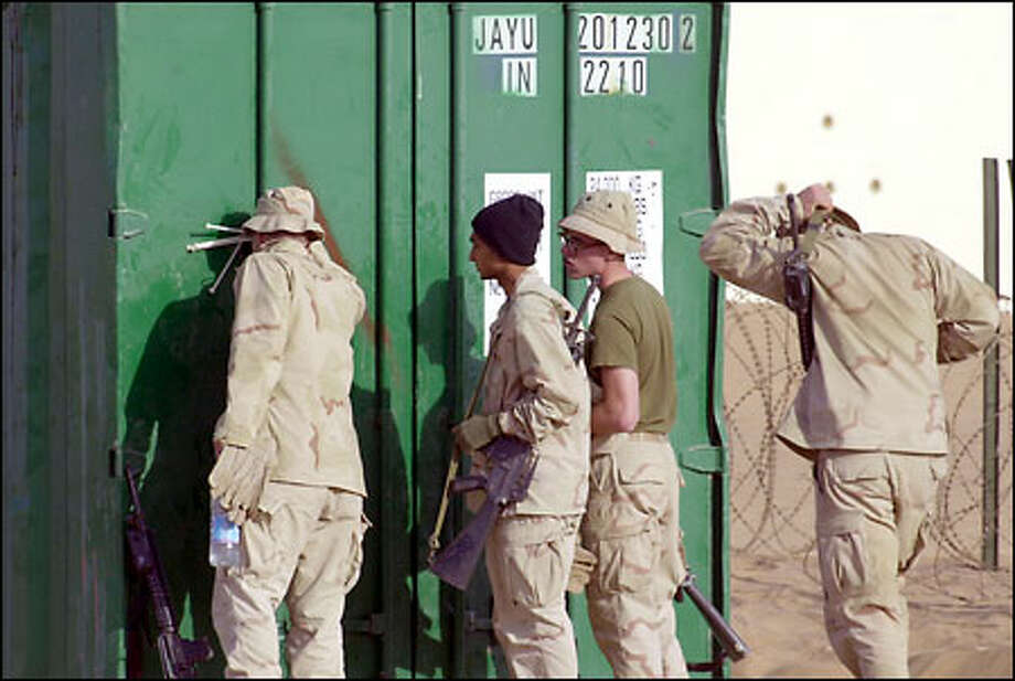 Marines speak to someone in a container, but who? Officials say the only detainee at the desert base is American John Walker, a Taliban fighter. Photo: Associated Press / Associated Press