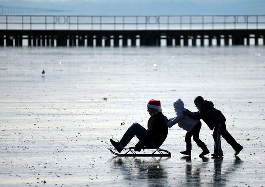 Scott Brackett is pushed by his children Laney and Brayden while sledding on the frozen water at Juanita Beach Park in Kirkland on Saturday. Photo: Thom Weinstein, Seattlepi.com / seattlepi.com
