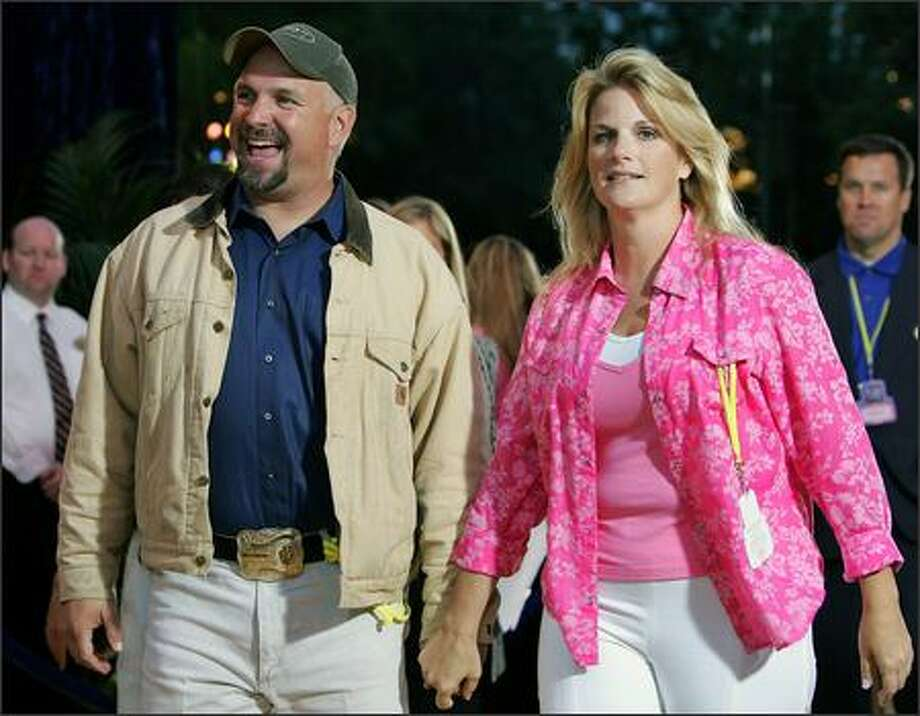 Country crooners Garth Brooks and Trisha Yearwood (seen here at Disneyland's 50th anniversary party in May) tied the knot on Friday. You may recall that fans swooned when Brooks (who has admitted to repeatedly cheating on his first wife) popped the question on stage four months ago. Good luck, Trisha! Photo: Associated Press / Associated Press