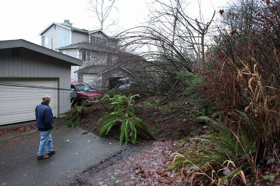 A neighborhood resident examines a landslide that came crashing down against a house on Monday, December 13, 2010 on Riviera Place NE along Lake Washington. The slide closed Riviera Place and the Burke-Gilman Trail, forcing bike commuters around the mess and up a steep hill. (Joshua Trujillo, Seattlepi.com). Photo: Joshua Trujillo, Seattlepi.com / seattlepi.com