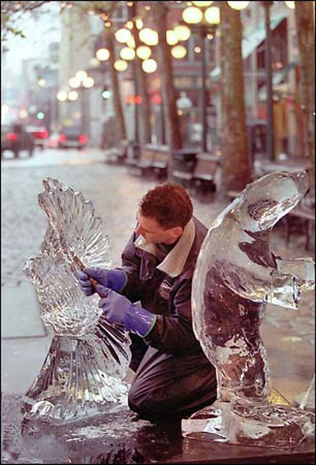 In what might be described as one of the coolest art forms around, Steve Cox, co-owner of Creative Ice Carvings, fashions a dove in Pioneer Place Park. Cox will be making ice images at the park from 4:30 to 6:30 p.m. Tuesday and Thursday. Photo: Phil H. Webber, Seattle Post-Intelligencer / Seattle Post-Intelligencer
