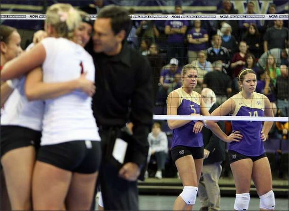 Washington's Jenna Hagglund, right, and Kindra Carlson watch as Nebraska's players and coach John Cook celebrate after defeating Washington during the NCAA Division I regional women's volleyball in Seattle on Saturday. Photo: Associated Press / Associated Press