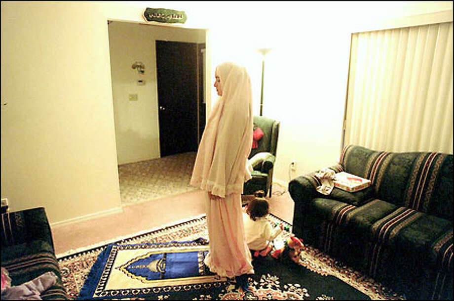 Mona Marouf prays in her Shoreline home, where she helps takes calls on a hot line for Arab Muslims reporting hostility in the wake of the Sept. 11 attacks. Photo: Meryl Schenker, Seattle Post-Intelligencer / Seattle Post-Intelligencer