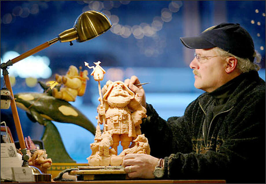 Dennis Brown is part of the window display at his Kirkland shop, where he sits at a workbench carving Santas out of polymer. Reasons to Believe is filled with thousands of Santas, which range from traditional to offbeat. Photo: Paul Joseph Brown, Seattle Post-Intelligencer / Seattle Post-Intelligencer