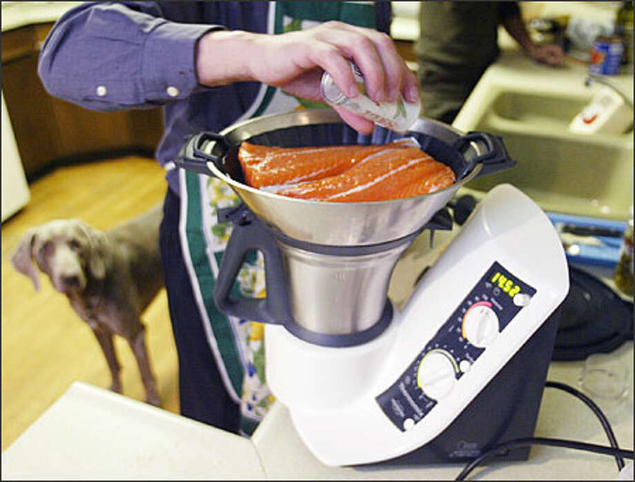 Angelo Papa, regional Thermomix salesman, seasons salmon fillets for steaming as he demonstrates the machine's uses. Photo: Mike Urban, Seattle Post-Intelligencer / Seattle Post-Intelligencer